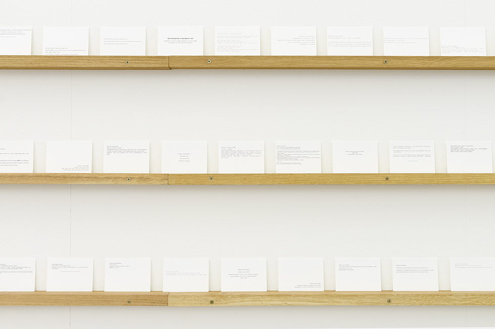 White wall with three rows of index cards on shelves in close up.