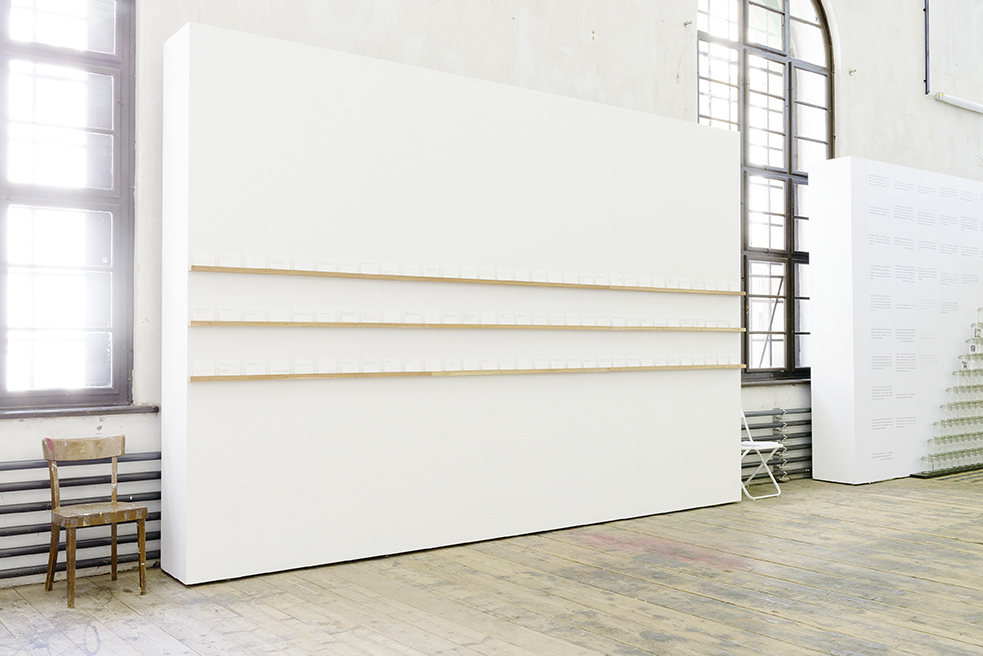 White wall with three rows of index cards on shelves at eye level.